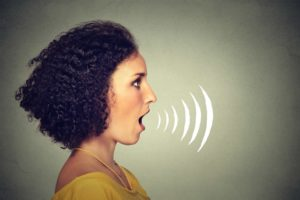 Woman singing with sound waves coming out of her mouth