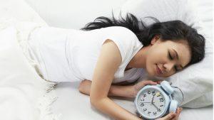 Woman sleeping with alarm clock